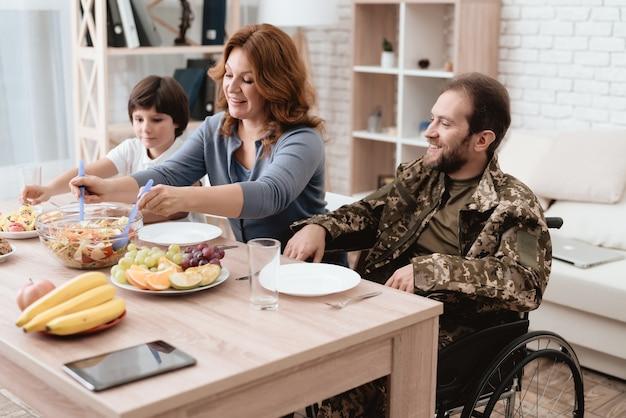 Um homem de uniforme está sentado à mesa da cozinha.