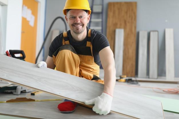 Um homem de uniforme muda o revestimento do piso, nas mãos um laminado. o reparador de capacete sorri. consertos domésticos