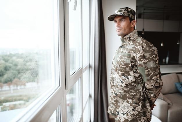 Um homem de uniforme usa uma grande janela panorâmica