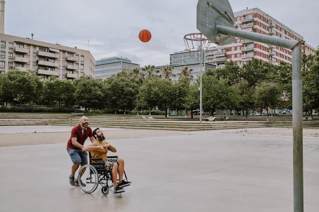 Um homem deficiente em cadeira de rodas joga cesta com um amigo
