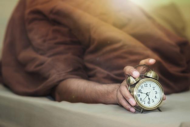 Um homem deitado debaixo de um cobertor marrom está saindo do despertador com sonolência.
