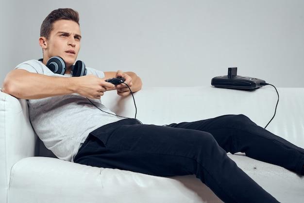 Um homem deitado no sofá com fones de ouvido enquanto joga videogame