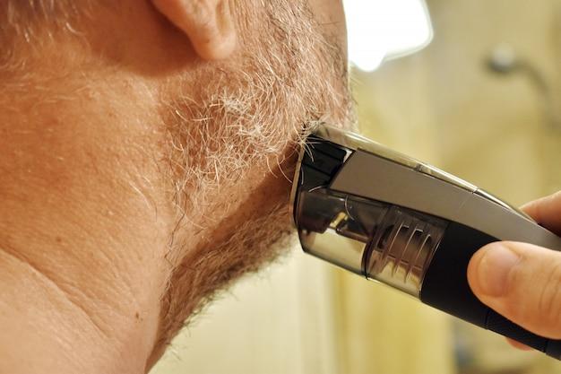Um homem depila a barba com um barbeador elétrico na frente de um espelho