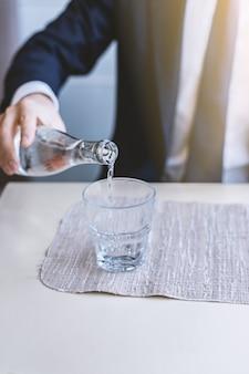 Um homem derrama a água de uma garrafa em um copo vazio transparente.