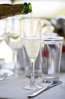Um homem derrama champanhe em uma taça