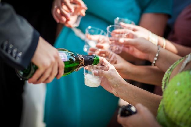 Um homem derrama champanhe nos copos. os convidados do casamento servem champanhe.
