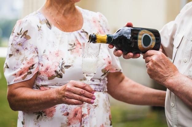 Um homem derrama champanhe ou vinho branco em um copo de sua amada, bebidas alcoólicas, comemoração de aniversário, aniversário