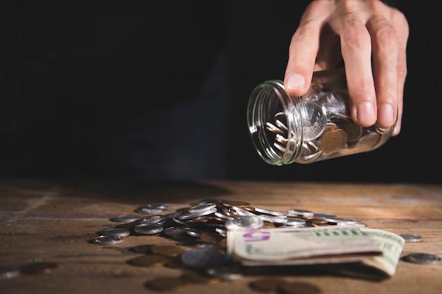 Um homem derrama moedas de uma jarra de vidro em uma mesa de madeira