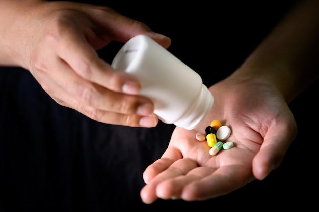 Um homem derramar remédio na mão para tratamento de doenças, medicamentos e drogas