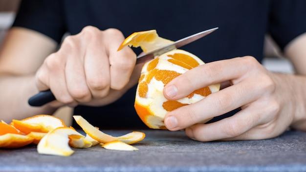 Um homem descascando uma laranja usando uma faca em uma placa de cozinha