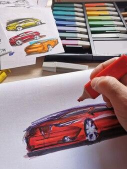 Um homem desenha um novo projeto de design para um futuro carro em casa