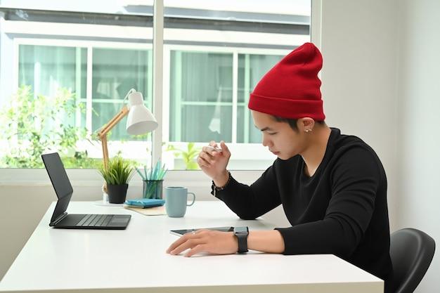 Um homem designer gráfico com chapéu de lã vermelha está trabalhando em um tablet gráfico na mesa do escritório
