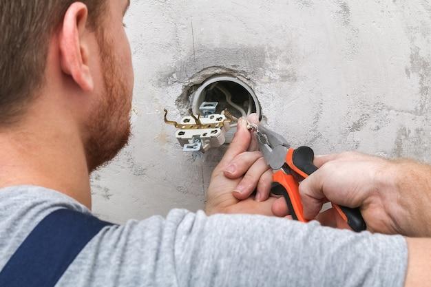 Um homem desmonta e conserta uma tomada elétrica para reparos. tomada de alimentação.