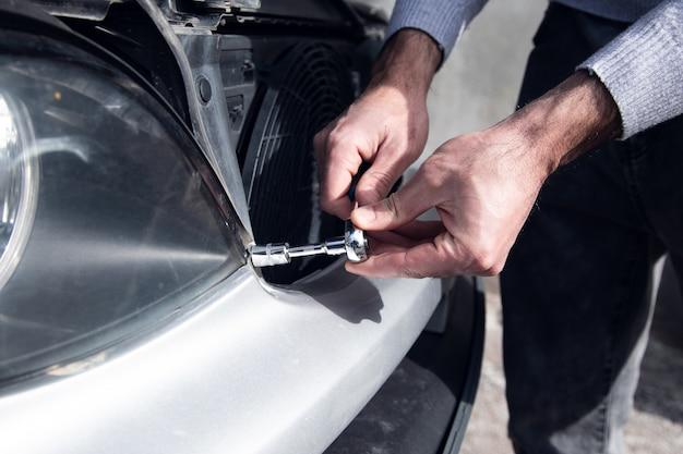 Um homem desmonta os faróis de um carro