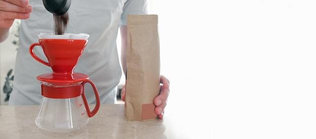 Um homem despeja café recém-moído de um saquinho em um gotejador. um kit profissional para servir em casa