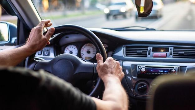 Um homem dirigindo um carro com cigarro