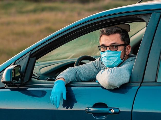 Um homem dirigindo um carro com uma máscara protetora e luvas no carro, se protege do vírus