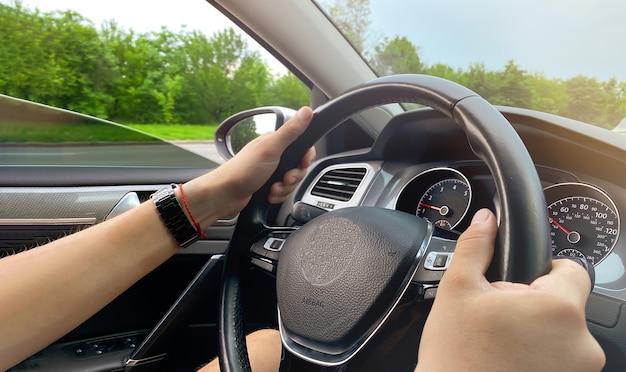 Um homem dirigindo um carro, passando por uma bela paisagem florestal. aluguel de carros, conceito de condução do carro.