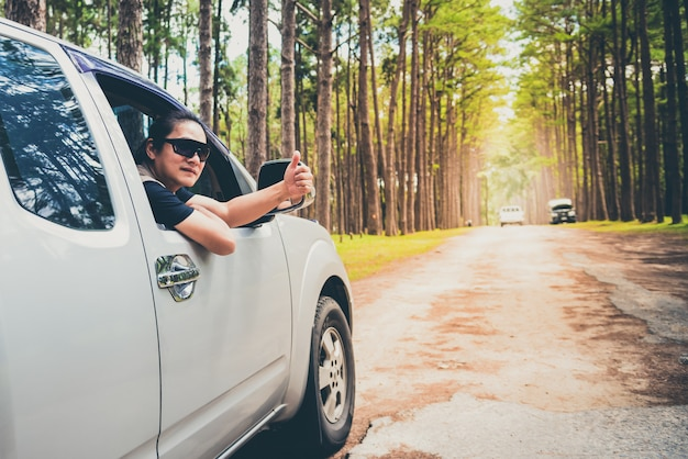 Um homem dirigindo uma caminhonete por caminhos irregulares que é um caminho no meio da floresta de pinheiros