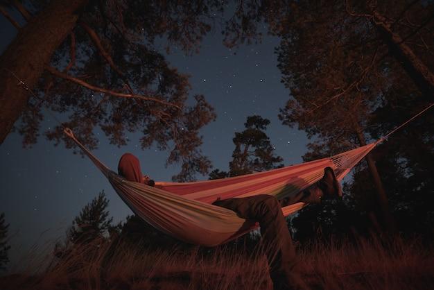 Um homem dorme em uma rede em uma noite estrelada. iluminação da fogueira. fotografia noturna