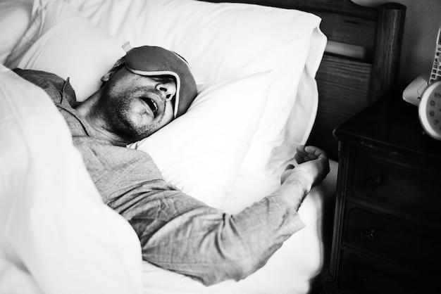 Um homem dormindo em uma cama