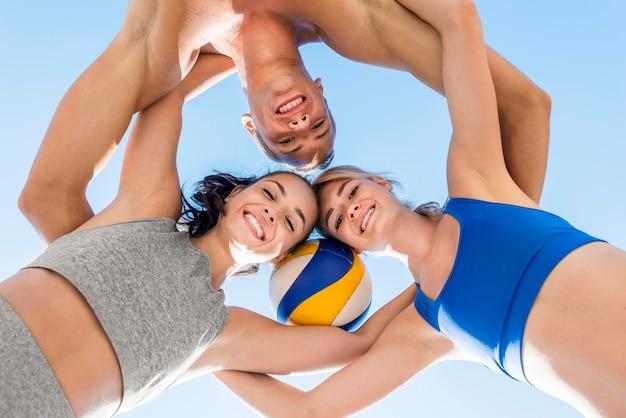 Um homem e duas mulheres posando juntos com vôlei