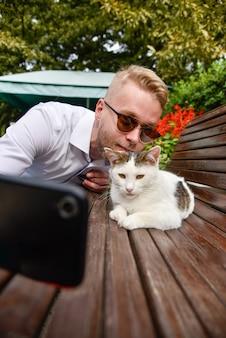 Um homem é fotografado com um gato de rua sentado em um banco
