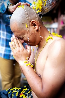 Um homem é ordenado de acordo com os princípios budistas com um corte de cabelo curto.
