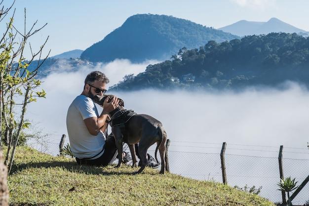 Um homem e um cachorro pit bull admirando a natureza e a grande neblina nas montanhas de petrópolis, brasil, cobrindo a cidade sob as nuvens. relação afetuosa entre humano e animal.