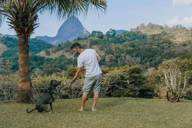 Um homem e um cão pit bull brincando e admirando a natureza e as montanhas de petrópolis, no rio de janeiro, brasil. relação afetuosa entre humano e animal.