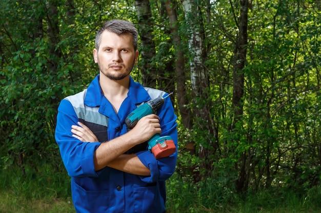 Um homem é um construtor em um manto com uma chave de fenda nas mãos