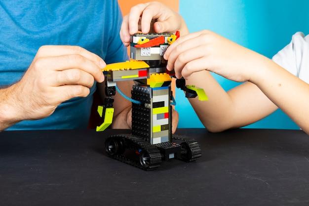 Um homem e um menino se reúnem a partir de um construtor de um robô. mãos masculinas e infantis coletam lego
