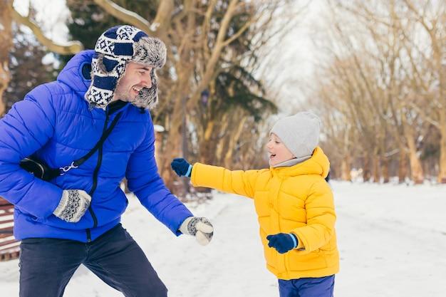 Um homem e uma criança aproveitam a neve no parque no inverno, pai e filho se divertem juntos