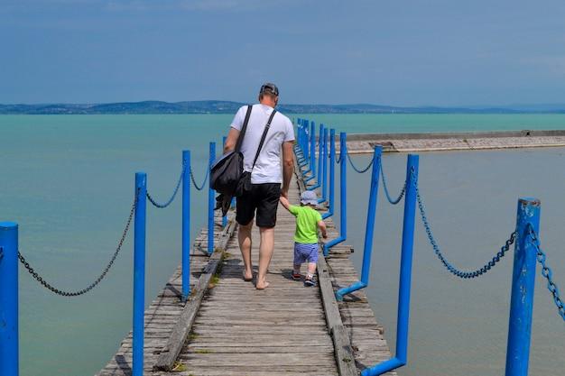 Um homem e uma criança caminham ao longo de um píer de concreto com coisas