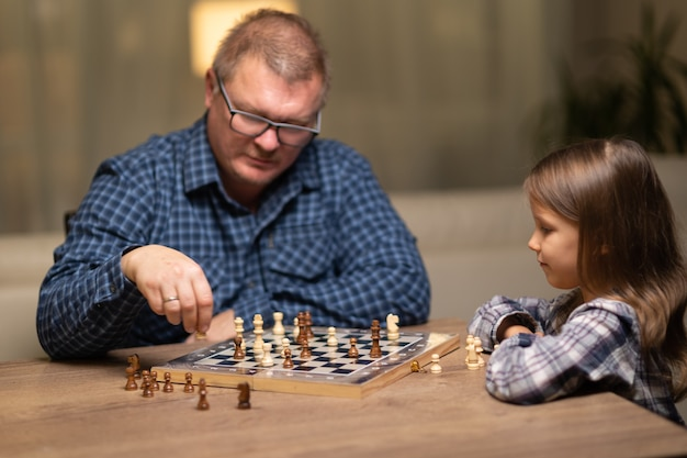 Um homem e uma criança jogam xadrez, o pai ensina a filha a jogar xadrez.
