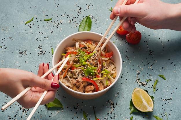 Um homem e uma menina comem macarrão asiático com carne de porco e vegetais juntos