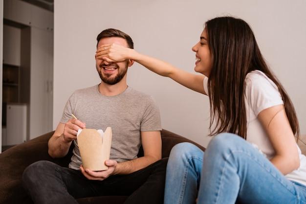 Um homem e uma mulher alegres passam bons momentos juntos em casa