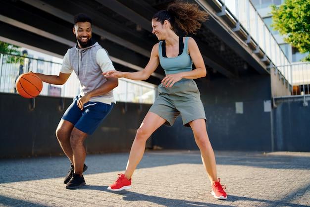 Um homem e uma mulher amigos jogando basquete ao ar livre na cidade.