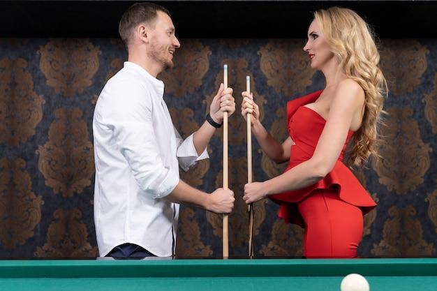 Um homem e uma mulher apaixonados com um sorriso e ternura olham um para o outro segurando um taco de madeira nas mãos enquanto estão de pé na mesa de bilhar