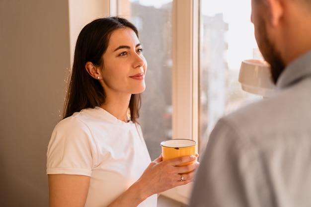 Um homem e uma mulher bebem chá perto da janela