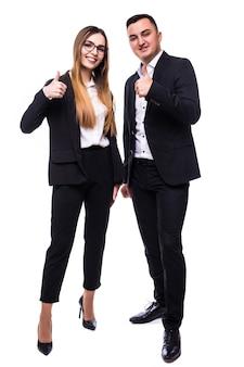 Um homem e uma mulher bonitos em uma suíte preta mostram sinal de positivo no branco