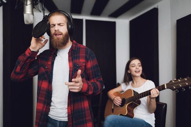 Um homem e uma mulher cantam uma música em um estúdio de gravação.
