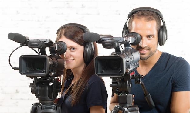 Um homem e uma mulher com câmeras de vídeo profissionais