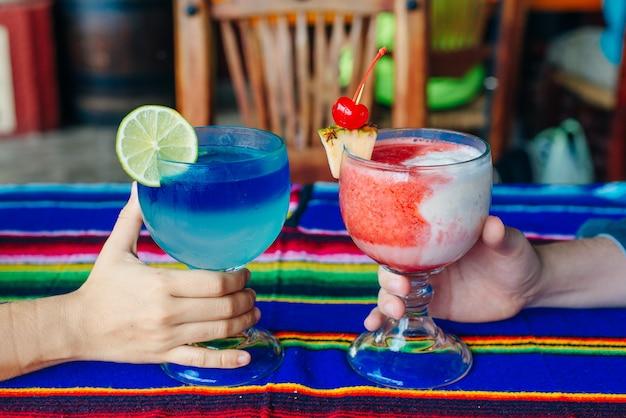 Um homem e uma mulher com coquetéis multicoloridos nas mãos no restaurante mexico.
