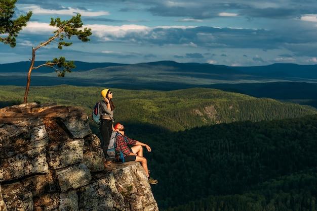 Um homem e uma mulher com mochilas na montanha admiram a vista panorâmica. um casal apaixonado em uma rocha admira as belas paisagens. viajantes nas montanhas ao pôr do sol. um casal em uma caminhada. copie o espaço