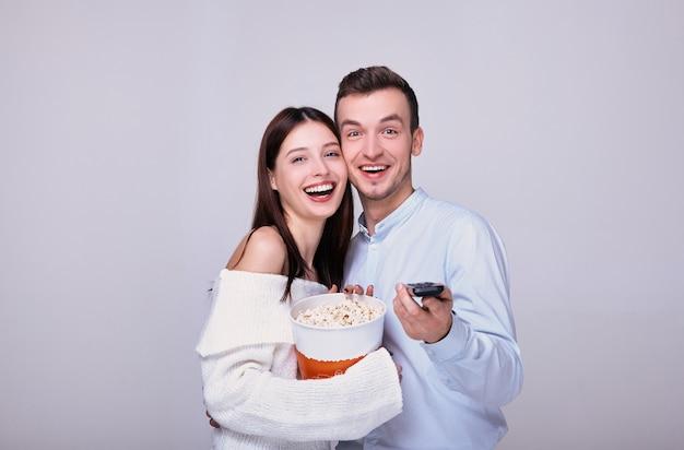 Um homem e uma mulher com um controle remoto de tv comem pipoca.