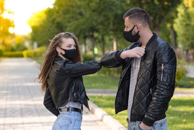 Um homem e uma mulher com uma máscara médica. o casal cumprimentando com um cotovelo. conceito de cuidados de saúde. covid19, coronavírus.