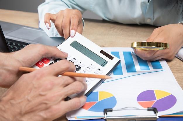 Um homem e uma mulher conversando sobre estatísticas em sua mesa