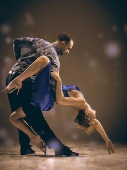 Um homem e uma mulher dançando tango argentino no fundo cinza do estúdio