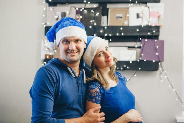 Um homem e uma mulher de chapéu azul de natal se abraçam.